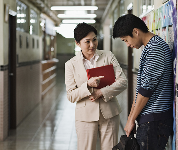 Woman Talking to Student in Hallway